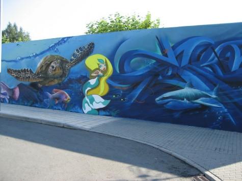 Graffiti solidario en la pared de las Piscinas Municipales