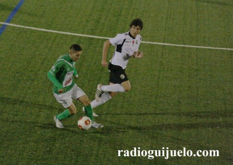 Rubén Peña conduce el balón ante la mirada de un jugador del Burgos C.F.