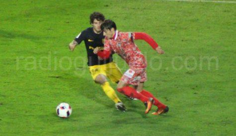 Luque ante la presencia de un jugador del Atlético de Madrid.